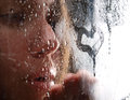 A girl slooking through the glass wet Royalty Free Stock Photo