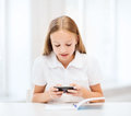 Girl with smartphone at school education technology and internet concept little student Royalty Free Stock Images