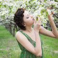 Girl smelling apple flowers Stock Photos