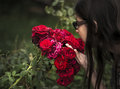 Girl is smelling a big red rose Royalty Free Stock Photo
