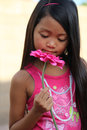 Girl smelling pink flower minority in outfit a large Royalty Free Stock Image