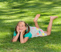 Girl smiles laying on grass a with long brown hair in pigtails and brown eyes who just lost her two front teeth as she lays the in Stock Images