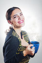 Girl smiling with cup of hot beverage a young woman cordially and holding a Royalty Free Stock Image