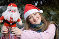 Girl smiling holding Santa doll Royalty Free Stock Photos