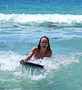 Girl smiling while riding a big blue wave on a body board on the blue sea on a sunny day. Royalty Free Stock Photography