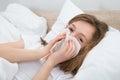 Girl sneezing in handkerchief sick on bed bedroom Stock Images