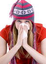 Girl sneezing to paper handkerchief in winter cap Stock Images