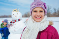 Girl with a snowman close up portait of happy beautiful outside in winter time Stock Photos