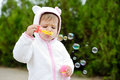 Girl and soap bubbles cute toddler blowing Stock Image