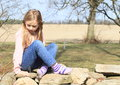 Girl in socks on wall sad little kid hairy blond pink jacket blue pants and sitting stone Stock Images