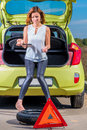 Girl with a spare wheel and tools near the car Royalty Free Stock Image