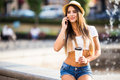 Girl speak on mobile phone with cup of coffee outdoors near fountain