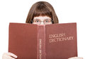 Girl with spectacles looks over English Dictionary Royalty Free Stock Photo