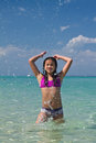Girl splashing in the water at the beach Royalty Free Stock Photo