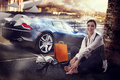 Girl and a sport car young is sitting on the pavement next to sports Royalty Free Stock Image