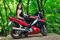 The girl on a sports bike in the woods sits motorcycle Stock Image