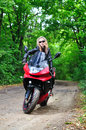 The girl on a sports bike in the woods sunglasses sits motorcycle Royalty Free Stock Photo