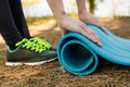 Girl in sports shoes spreads blue karemat in nature, for yoga, w