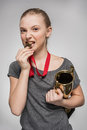 Girl in sportswear holding trophy and biting medal isolated on grey