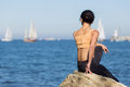 Girl in sportswear observes yachting regatta rear view brunette sitting on the rock young woman Stock Images