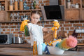 Girl with spray bottles and different cleaning supplies at home