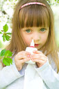 Girl spraying medicine in nose little drops spray Stock Images