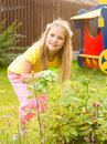 Girl sprays plants in the garden Royalty Free Stock Photo