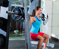 Girl squats in multipower squatting smith machine barbell at gym Royalty Free Stock Photos