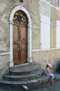 Girl on the stairs of an old building a modern preteen is waiting under closed door she is sitting stone house Stock Photos