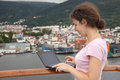 Girl stand on deck of ship with laptop Royalty Free Stock Photo