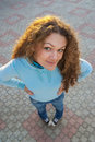 Girl stand on square tile beautiful woman with curly hair looks upwards and smiles Stock Images