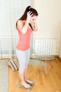 Girl standing on bathroom scales Royalty Free Stock Photo