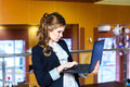 Girl standing in a cafe and working on laptop Royalty Free Stock Photo