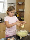 Girl standing in kitchen dipping finger into bowl of cake mix holding spoon Stock Photos