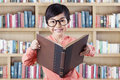 Girl standing in library while reading textbook friendly elementary school student the smiling on the camera and a Royalty Free Stock Image