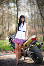 A girl is standing next to a motorcycle biker beautiful black haired woman in short skirt near sports bike female biker Royalty Free Stock Photography