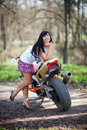 A girl is standing next to a motorcycle biker beautiful black haired woman in short skirt near sports bike female biker Royalty Free Stock Images