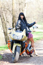 A girl is standing next to a motorcycle biker beautiful black haired woman in short skirt near sportsbike female biker Royalty Free Stock Photo