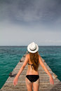 Girl standing at the pier enjoying the breeze from the sea a beautiful in black bikini and panama hat enjoys on caribbean beach Stock Image