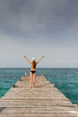 Girl standing at the pier raising her arms to the sky a young in bikini and panama hat raises on a wooden caribbean sea beach Royalty Free Stock Photos