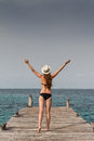 Girl standing at the pier raising her arms to the sky a young in bikini and panama hat raises on a wooden caribbean sea beach Stock Photos