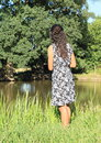 Girl standing by pond Royalty Free Stock Photo
