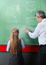 Girl standing with teacher wiping board rear view of little male in classroom Royalty Free Stock Image