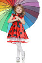 Girl standing under colorful umbrella Stock Photos