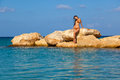 Girl is standingon stone standing on in sea Royalty Free Stock Photo