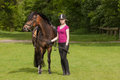 Girl stands besides her pony brown new forest on a meadow Stock Images