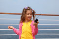 Girl stands on board ship holds portable radio Stock Photos