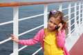 Girl stands on board ship, talks by portable radio Royalty Free Stock Photo