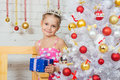 A girl stands at a Christmas fir-tree with gift in hand Royalty Free Stock Photo