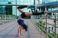 Girl stands on the hands upside down acrobatics in foreground performing yoga and Royalty Free Stock Photos